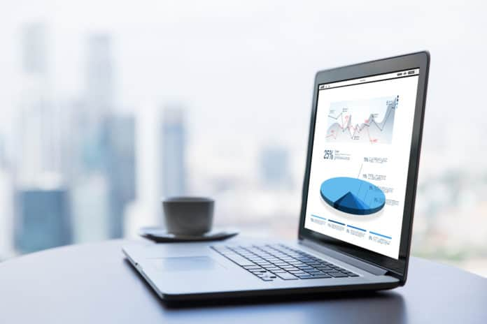 technology, statistics, economics, business and modern life concept- close up of open laptop computer with charts on screen and coffee cup on table at office or hotel room