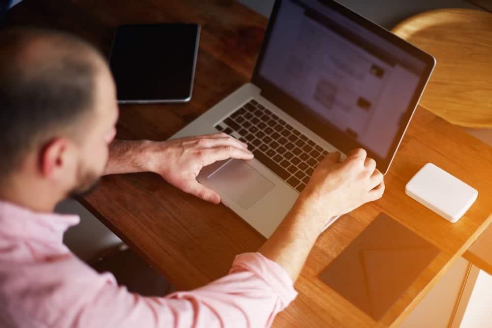 Male student using digital computer