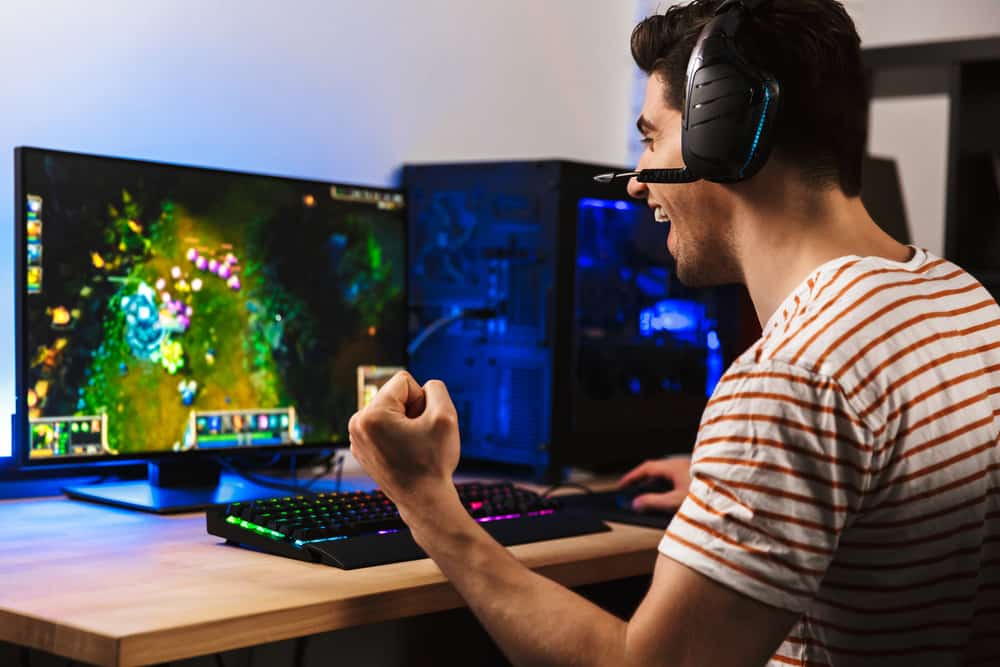 Portrait of delighted young guy playing video games on computer wearing headphones and using backlit colorful keyboard
