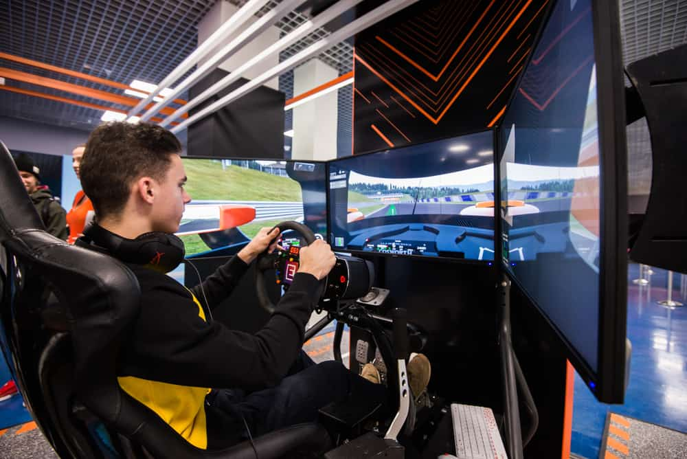 Simulation of race car video player game with big screen monitors and cockpit controls like a racing car
