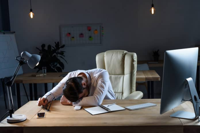 Tired businessman sleeping at working table in dark office
